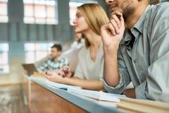 Studenter som lyssnar till föreläsningen på universitetet royaltyfri foto