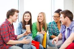 Studenter som meddelar och skrattar på skolan Arkivbilder