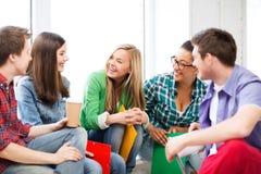 Studenter som meddelar och skrattar på skolan Fotografering för Bildbyråer