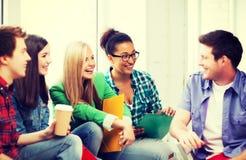 Studenter som meddelar och skrattar på skolan Arkivbild