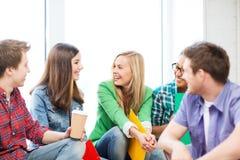 Studenter som meddelar och skrattar på skolan Royaltyfri Fotografi