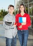 Studenter som rymmer böcker, medan stå i högskola Arkivbild