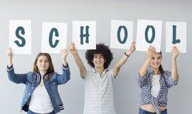 Studenter som rymmer det skriftliga banret för skola Fotografering för Bildbyråer