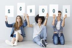 Studenter som rymmer det skriftliga banret för skola Royaltyfria Bilder