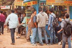 Studenter som söker efter de olika böckerna på den utomhus- boken, marknadsför Royaltyfria Bilder