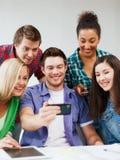 Studenter som ser in i smartphonen på skolan Arkivbild