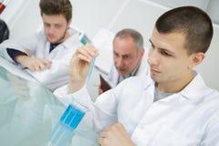 Studenter som ser kemisk flytande för reaktion i labb Royaltyfri Bild