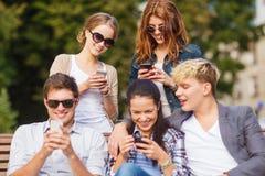Studenter som ser smartphones och minnestavlaPC Arkivfoto
