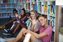 Studenter som sitter i arkiv och vinkande händer royaltyfri foto