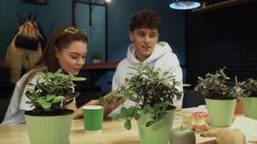 Studenter som sitter i ett kafé, läste en bok och en pratstund Fritid av ungdomarsom leder en sund livsstil stock video
