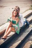 Studenter som sitter med en bok på gatan Royaltyfri Bild