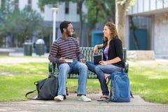 Studenter som sitter på bänk på universitetsområdet Royaltyfri Bild