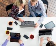 Studenter som sitter på tabellen genom att använda datorer och minnestavlor Arkivfoto