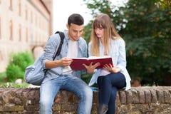 Studenter som sitter utomhus- läsning en bok Arkivfoto