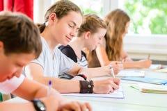 Studenter som skriver ett prov, i att koncentrera för skola Royaltyfri Fotografi