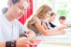 Studenter som skriver ett prov, i att koncentrera för skola Arkivfoto