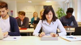 Studenter som skriver på den minnestavladatoren och bärbara datorn arkivfilmer