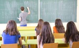 Studenter som studerar i klassrum arkivfoto