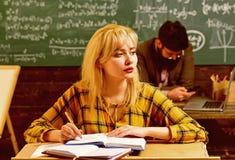 Studenter som studerar och testar kurs från lärare i klassrum på universitetet Studenten söker efter att studera metod det royaltyfri foto
