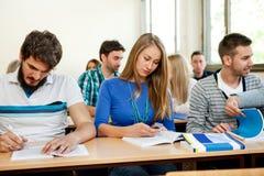 Studenter som tar anmärkningar i ett klassrum Royaltyfri Foto