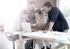 Studenter som teamworking på en bärbar dator Arkivbild