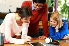 Studenter som tillsammans använder minnestavladatoren Arkivbild