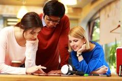 Studenter som tillsammans använder minnestavladatoren Arkivfoton