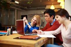 Studenter som tillsammans gör läxa med bärbara datorn Arkivfoton