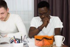 Studenter som tillsammans studerar, studenter som hemma studerar Arkivbild