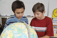 Studenter som undersöker ett jordklot Royaltyfri Bild