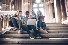 Studenter spenderar tid tillsammans Multietnisk grupp av ungdomarsom ser en bärbar dator och och sitter på moment i universitet royaltyfri bild