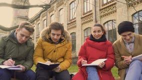 Studenter talar sammanträde på bänken parkerar in nära universitet stock video