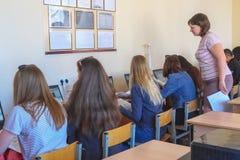 Studentes in een computerklasse met een leraar royalty-vrije stock afbeelding