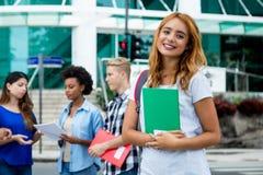 Studentessa abbastanza americana con il gruppo di peopl internazionale immagini stock