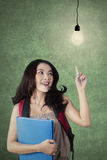 Studentessa abile che indica alla lampadina Fotografia Stock