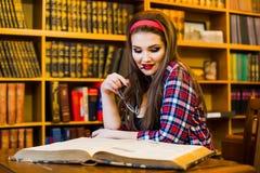 Studentessa abile con la ragazza di vetro che si siede nella biblioteca con i libri Fotografia Stock