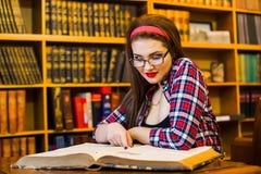 Studentessa abile con la ragazza di vetro che si siede nella biblioteca con i libri Immagine Stock Libera da Diritti