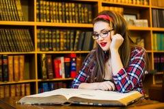 Studentessa abile con la ragazza di vetro che si siede nella biblioteca con i libri Fotografia Stock Libera da Diritti