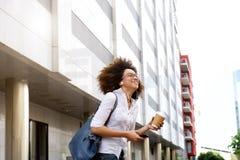Studentessa africana sorridente che cammina con il cellulare Fotografia Stock