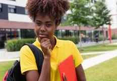 Studentessa afroamericana astuta all'aperto sulla città universitaria Fotografia Stock