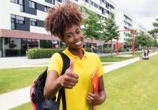 Studentessa afroamericana che mostra pollice all'aperto sulla città universitaria Fotografia Stock Libera da Diritti