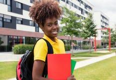 Studentessa afroamericana di risata all'aperto sulla città universitaria Fotografia Stock