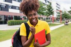 Studentessa afroamericana felice all'aperto sulla città universitaria Immagini Stock