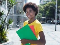 Studentessa afroamericana moderna in una camicia gialla Immagine Stock