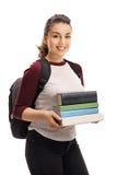 Studentessa allegra che tiene una pila di libri Fotografia Stock