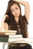 Studentessa americana asiatica sveglia che esamina i libri Immagini Stock Libere da Diritti