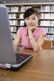 Studentessa annoiata che per mezzo del computer portatile Fotografia Stock