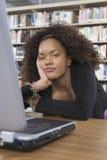 Studentessa annoiata che si siede allo scrittorio delle biblioteche Fotografia Stock