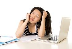 Studentessa asiatica annoiata sovraccaricata sul computer Immagine Stock