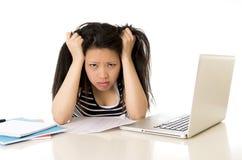 Studentessa asiatica annoiata sovraccaricata sul computer Immagini Stock